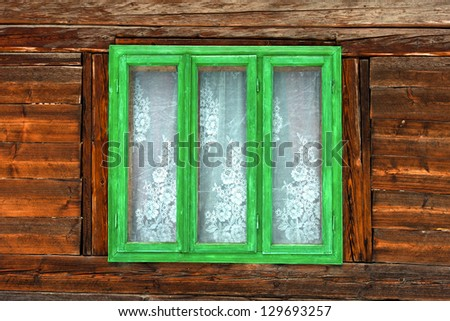 Green frame window of the old rustic house on the background of wooden walls