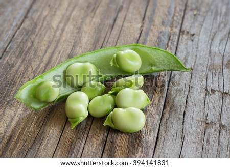 green fresh broad  beans on old wooden table