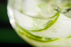 Green fresh cucumber drink closeup with small bubbles and ice cubes in a round glass
