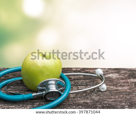 Green fresh organic natural nutrient apple with doctor\'s stethoscope heart shape on grunge old aged wood background blur bokeh:  World health day WHD symbolic conceptual design idea for healthy food