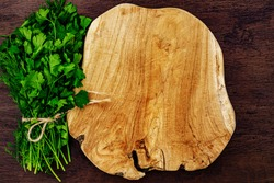Green fresh parsley and dill with wooden cutting board, copy space, mock up. Bunch of fresh parsley dill near wooden Board for recipe text place.