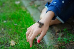 Green frog sitting on little girl hand. Child holding frog in the harden outside.Kid learning about nature.