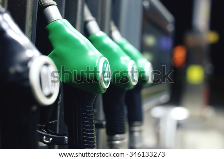 Green fuel pistols on fuel station.