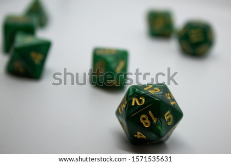 Green gaming dice with gold numbering on a white background. The D20 gaming dice sits in focus in the foreground. These dice are often associated with Dungeons and Dragons and other tabletop games. #1571535631