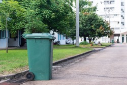 Green garbage bin in front of the house.Public trash on the side of the road.Infectious control concept.