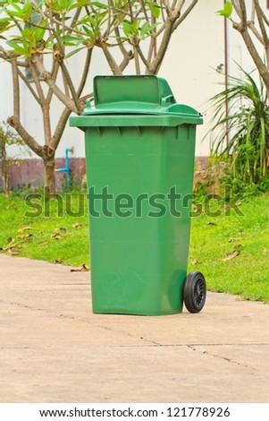 Green garbage bin with wheels on road