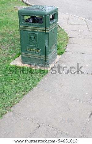 green garbage can on a garden grass background