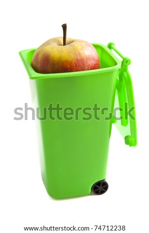 Green garbage container with apple isolated over white