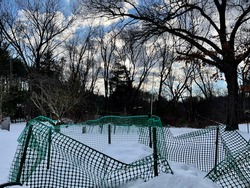 Green garden fence in white snow, a peaceful sunset moment during Christmas 2020 at a small town New England