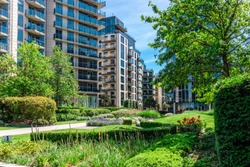 Green garden within apartment building complex in Battersea Reach during summer time.