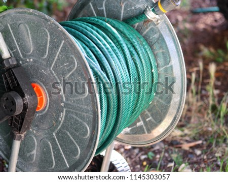 Green gardening hose for watering flowers and grass wrapped around the aluminum carrier. Garden watering hose compressed. Garden hose for watering plants in garden. Hanging water tube.