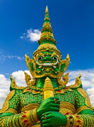 Green giant golden statue stands majestically towering magnificent blue sky and white clouds.