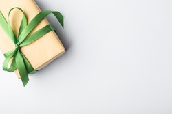 Green gift box with green ribbon and bow on a white background, place for the inscription free
