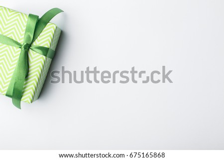 Green gift box with green ribbon and bow on a white background, place for the inscription free #675165868