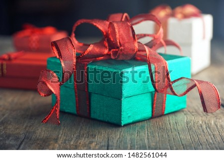 Green gift box with red ribbon for party on the the table.