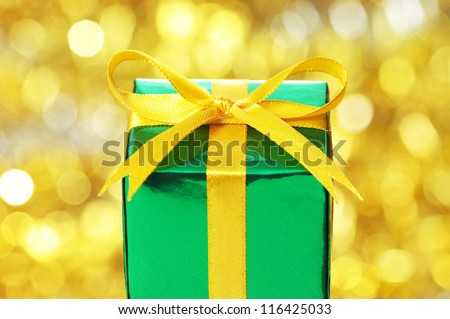 Green gift on red blurry lights background. - stock photo