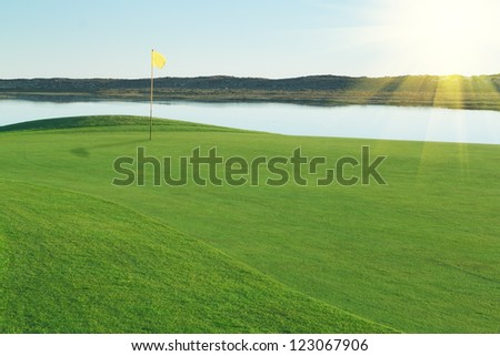 Green glade golf course, with a yellow flag.