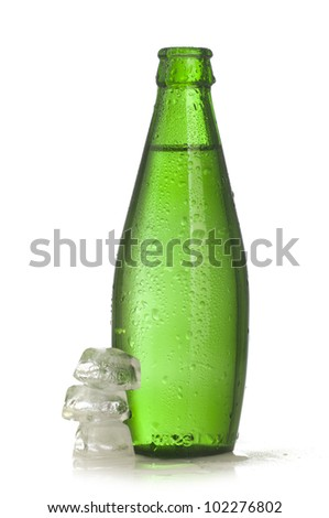 Green glass bottle of mineral water with ice on white background