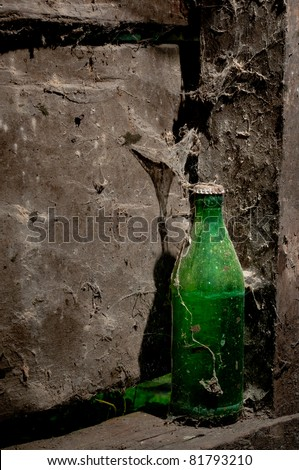 Green glass old bottle with dust and spider webs forgotten on a porch in a abandoned house in a remote and isolated village