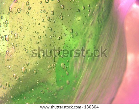 green glass vase with bubbles under running water