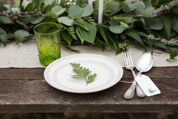 Green glass, white plate with green leave, silver spoon and fork with blank label and green leaves and eucalyptus on background outdoors