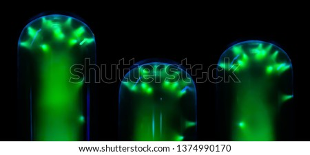 green glowing of electrical discharges in flasks with inert gas on a black background, resembling fantastic plants #1374990170