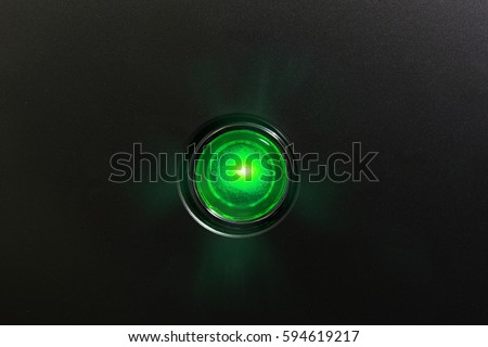 Green glowing status indicator, warning lamp or button, on black panel.