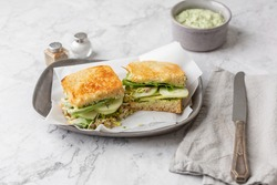 Green Goddess Sandwich on a Pewter Tray on a white Marble Countertop; Bowl of Green Goddess Dressing, Salt and Pepper, Knife, and Gray Napkin in Background