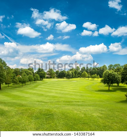 green golf field and blue cloudy sky. european landscape