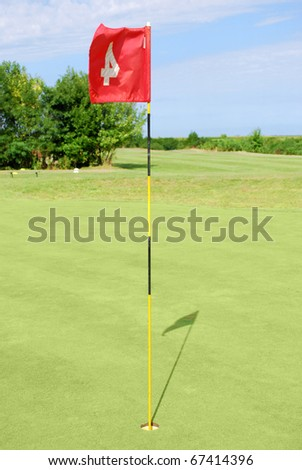 green golf field with red flag