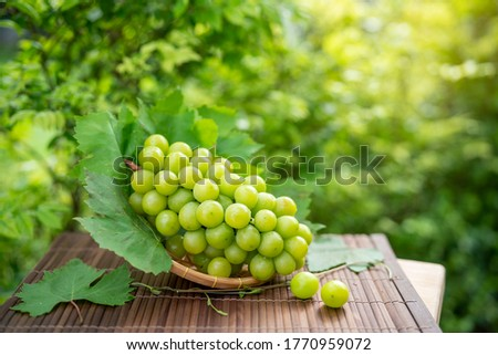 Photo of  Green grape in Bamboo basket on wooden table in garden, Shine Muscat Grape with leaves in blur background