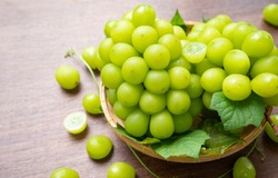 Green grape in Bamboo basket on wooden table in garden, Shine Muscat Grape with leaves in wooden background