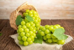 Green grape in Bamboo basket on wooden table in garden, Shine Muscat Grape with leaves in wooden background.