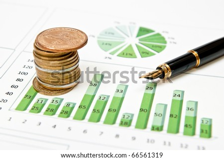 Green graph, chart and pen with stacks of coins