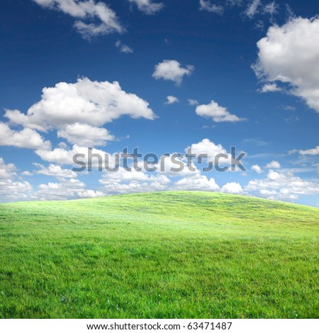 Green grass and blue sky with white clouds background