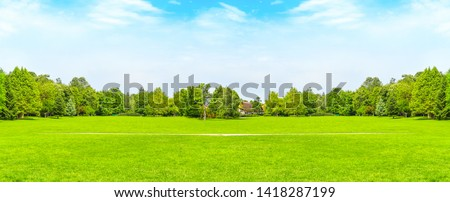 Green grass and green trees in beautiful park with white clouds blue sky in noon. Styled stock photo with golf course playground in a sunny summer day  perfect for banner or background.