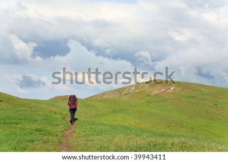 green grass covered summer mountainside, tourist on footway and cloudy sky