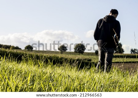 green grass in the countryside and man walking in the back