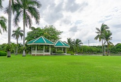 Green grass lawn in front gazebo, palm tree and greenery trees on background under cloudy sky in garden of public park