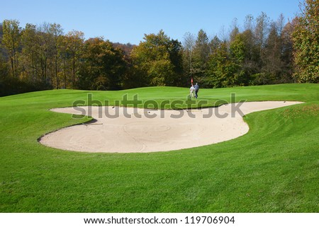 green grass of the golf course surrounded by autumnal forest