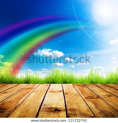 Green grass on wooden plank over a blue sky. Beauty natural background