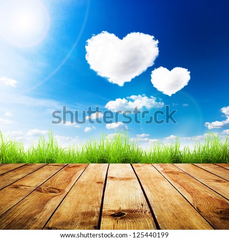 Green grass on wooden plank over a blue sky with hearts shape clouds Beauty natural background