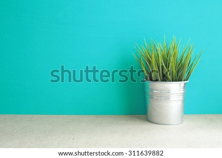 Green grass plant in vintage pot on table  front mint green background. Interior Decorating Item. Vintage effect.