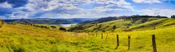 Green grazing farm land around Lake Lyell in Blue Mountains of Australia - life style agricultural cattle paddock fenced on hillsides in wide panoramic view.