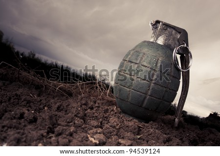 green grenade resting on a battlefield