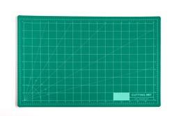 Green grid cutting matt or pad on background.