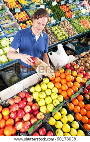 Green grocer putting red apples in a brown paper bag