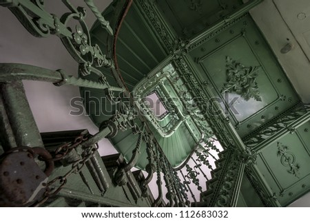 Green, grunge staircase in an old, dark building