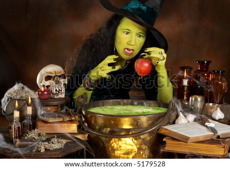 Green halloween witch putting a red apple in a cauldron with poisonous soup