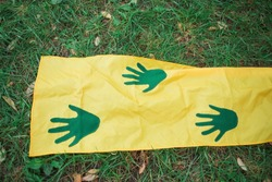 Green handprints on yellow long fabric on green grass. Playgame. Closeup.
